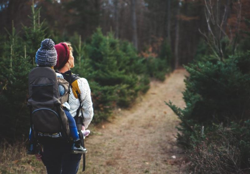 Photo of a woman hiking with a young child in a backpack.